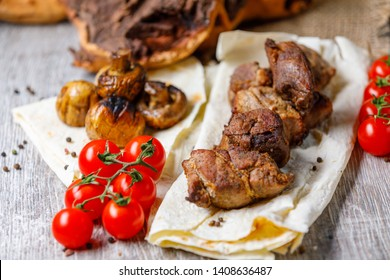 Fast food. Eastern food. Shish kebab, lyulya-kebab, shaverma, pita gyros. Dishes of oriental cuisine lying on pita bread and decorated with greens and vegetables, sauces and French fries