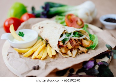 Fast food. Eastern food. Shish kebab, lyulya-kebab, shaverma, pita gyros. Dishes of oriental cuisine lying on pita bread and decorated with greens and vegetables, sauces and French fries.