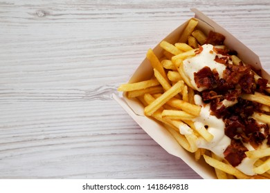 Fast food: french fries with cheese sauce and bacon in a paper box, view from above. Flat lay, top view.