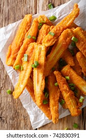 Fast food: fried baby corn with green onions close-up on the table. Vertical top view from above