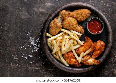 Fast food fried crispy and spicy chicken legs, wings and french fries potatoes with salt and ketchup sauce served in stone plate over dark texture background. Top view, space for text