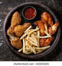 Fast food fried crispy and spicy chicken legs, wings and french fries potatoes with salt and ketchup sauce served in stone plate over dark texture background. Top view. Square image