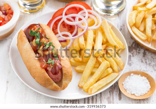 fast food - hot dog with French fries and chips on wooden table, top view
