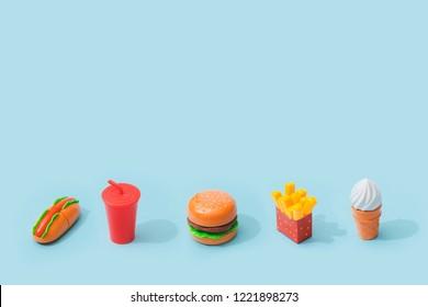 Fast food items on pastel blue background. Junk food minimal concept.