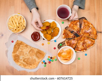 Fast food junk food concept. Kid eating nuggets, pizza, chips and other fast food.