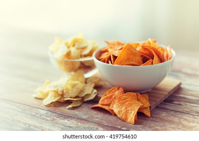 fast food, junk-food, cuisine and unhealthy eating concept - close up of crunchy potato crisps and corn crisps or nachos in bowls