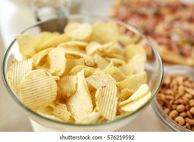 fast food, junk-food and unhealthy eating concept - close up of crunchy potato crisps in glass bowl and other snacks