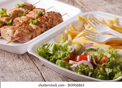 Fast food: kebabs, fries and fresh salad in tray close-up on the table. horizontal