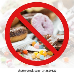 fast food, low carb diet, fattening and unhealthy eating concept - close up of chocolate pieces, jelly beans and glazed donuts behind no symbol or circle-backslash prohibition sign