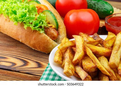 Fast food meal, hot dog, french fries, ketchup, tomato and cucumber on wooden background