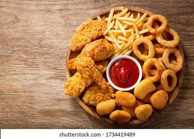 Fast Food: Zwiebelringe, Pommes frites, Hühnernuggets und gebratenes Hühnchen auf Holztisch, Topsicht