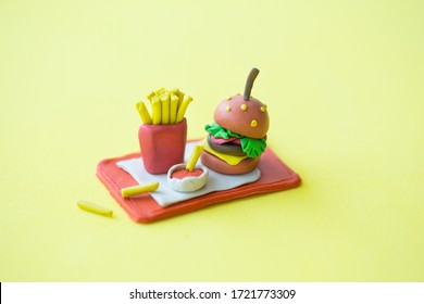 Fast food miniature items on pastel yellow isolated background. Junk food minimal concept. Burger and french fries on a red tray.  Plasticine sculptures. Creative conceptual art still life for banner.