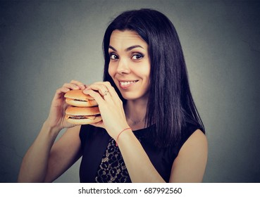 Fast food is my favorite. Woman eating a double cheeseburger enjoying the taste