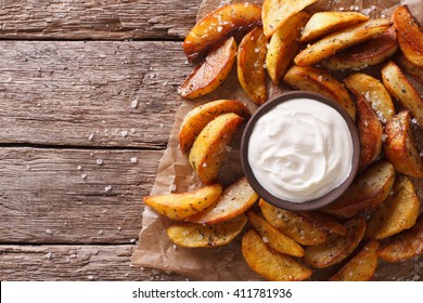Fast food: Potato wedges and mayonnaise on the table. horizontal top view