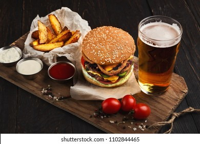 Fast food restaurant dish. Juicy burger, potato wedges, sauces and glass of cold beer on dark wooden background