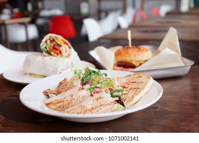 Fast food restaurant dishes - healthy chicken sanad and not so healthy burger and meat roll
