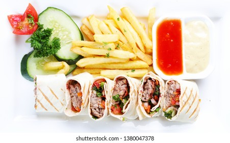 fast food, saj kebab, shish kebab, and decorated with greens and vegetables, sauces and french fries