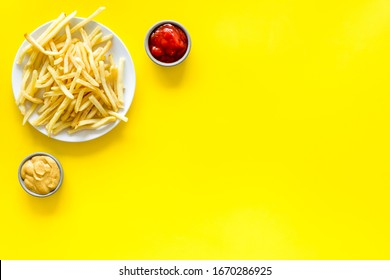 Fast food symbol. French fries on plate on yellow table top-down copy space