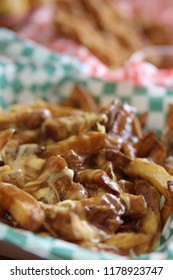 Fast food take out of Canadian poutine with cheese melting over French fries with beef gravy in a basket ready to eat