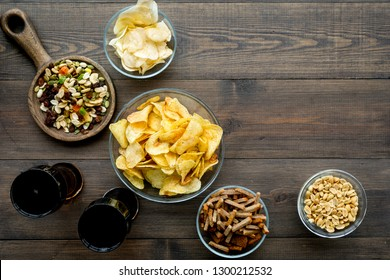 Fast food for TV watching. Snacks on desk.  Chips, nuts, rusks and soda on dark wooden background top view copy space