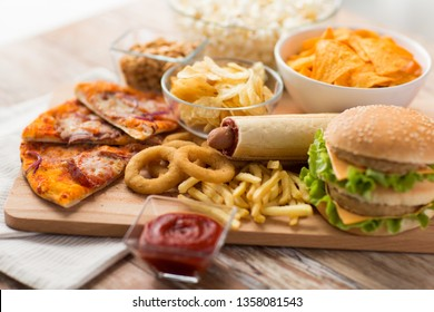 fast food and unhealthy eating concept - close up of double hamburger or cheeseburger, deep-fried squid rings, french fries, pizza and chrisps on wooden board