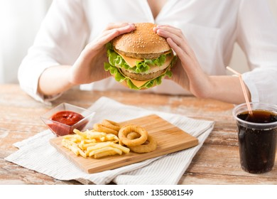 fast food and unhealthy eating concept - close up of woman with double hamburger or cheeseburger, deep-fried squid rings, french fries and cola drink at quick service restaurant