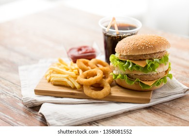 fast food and unhealthy eating concept - close up of double hamburger or cheeseburger, deep-fried squid rings, french fries, cola drink and ketchup on wooden board