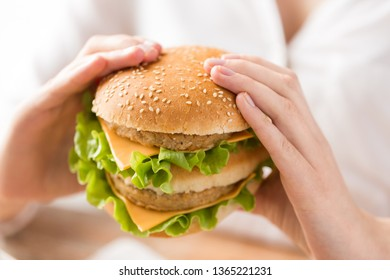 fast food and unhealthy eating concept - close up of woman holding hamburger