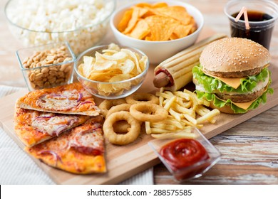 fast food and unhealthy eating concept - close up of fast food snacks and cola drink on wooden table - Shutterstock ID 288575585
