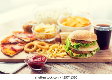fast food and unhealthy eating concept - close up of hamburger or cheeseburger, deep-fried squid rings, french fries, drink and ketchup on wooden table