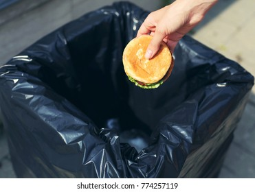 Fast food and unhealthy eating concept - hand throwing a burger in the trash on street