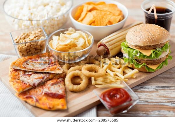 ファストフードと不健康な食べ物のコンセプト – 木のテーブルの上のファストフードのスナックやコーラの飲み物の接写