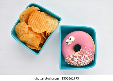 Fast food, unhealthy snacks, donut and potato chips in lunch box, top view. Unhealthy kids eating.