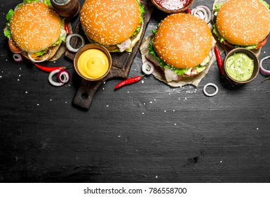 Fast food. Various burgers with sauces. On the black chalkboard.