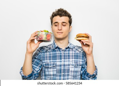 fast food versus healthy food concept with young man holding a salad in one hand and hamburger in the other one, isolated on white