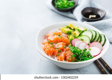 Fast and healthy food, lunch, nutrition concept. Fresh organic hawaiian salmon poke bowl with rice, seaweed, avocado, cucumber on a modern kitchen table