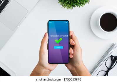 Fast Money Transfers. Woman Holding Smartphone With Transaction Completed Message On Screen, Sitting At Desk In Office, Top View