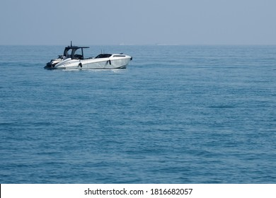Fast motor boat in silver color with a jet ski on Board against the background of sea yachts and blue sky at anchor in the sea.