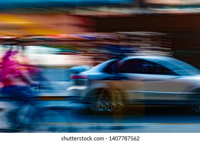 fast moving /motion of a blurry  car and a bicycle on the road. Long exposure and slow shutter speed explained.