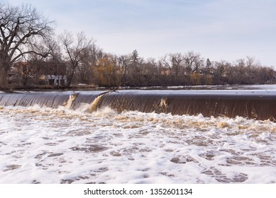 Fast moving river water flowing over concrete dam. Ice floes and chunks falling into brown water over hydro electric plant.