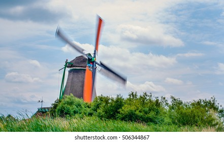 Fast moving windmill blades moving as wind blows past it in rural area. Includes copy space.