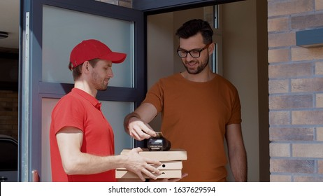 Fast pizza delivery. View young courier carrying pizza boxes knocking on door waiting for customer. Handsome positive man opening door taking order paying with credit card.