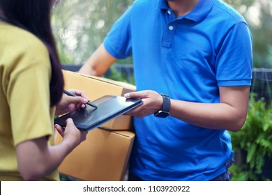 Fast and reliable service. Asian young woman signing on tablet pc computer at the entrance of her home. delivery man brings delivering parcel box.
