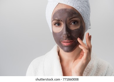 Fast result. Portrait of confident lady in bathrobe and towel on head is looking at camera with joy while touching her face with clay mask while using anti-aging procedures. Isolated. Beauty concept