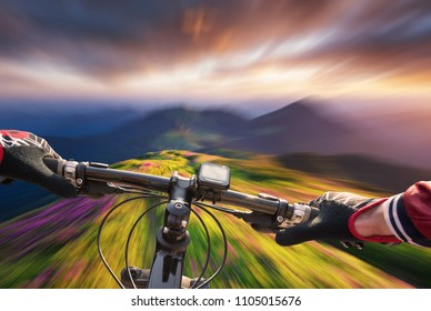 Fast ride on bike in mountain valley during sunset. Sport and active life concept