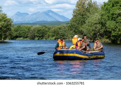 FAST RIVER, KAMCHATKA PENINSULA, RUSSIAN FAR EAST - JULY 25, 2016: Summer rafting on Kamchatka - group of tourists, travelers floating on calm river on raft on background of mountains and green forest