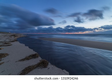 Fast river on the sandy beach. Sunset on the seashore.