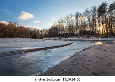 Fast river on the sandy seashore.