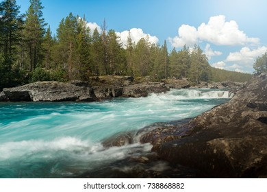 Fast river running through green forest in Norway, Europe. Blue sky with clouds in background.