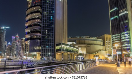 Fast run on promenade of Dubai Marina with view of bridge and modern Towers reflected in water in Dubai night timelapse hyperlapse, United Arab Emirates. Dubai Marina is a district in Dubai and an